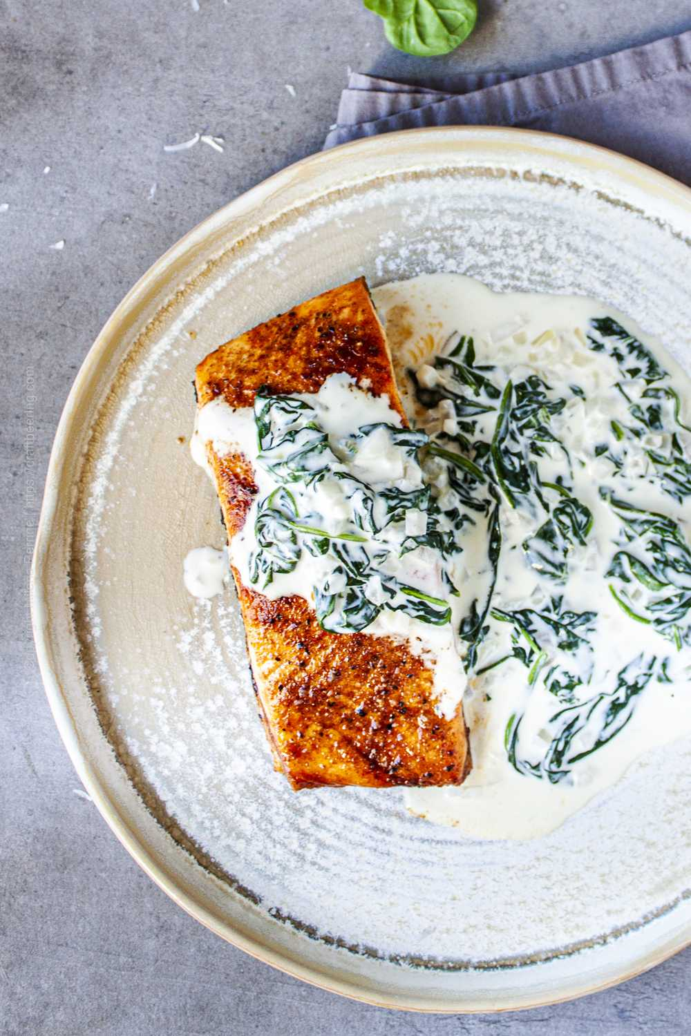 Pan seared salmon fillet topped with creamy spinach sauce.