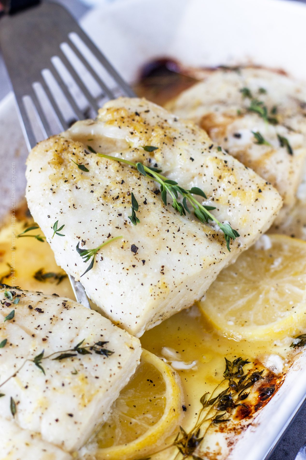 Baked cod fillets in oven with lemon and thyme.