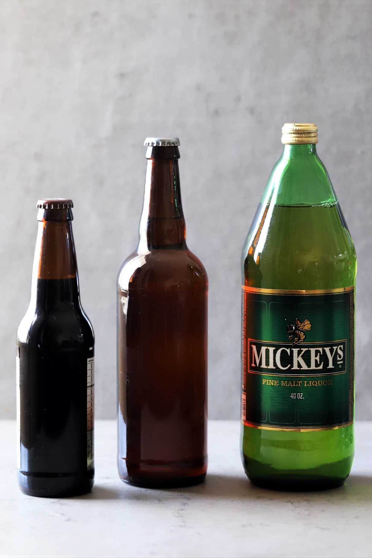 40 ounce malt liquor next to a pint beer bottle and a 12 oz beer bottle.