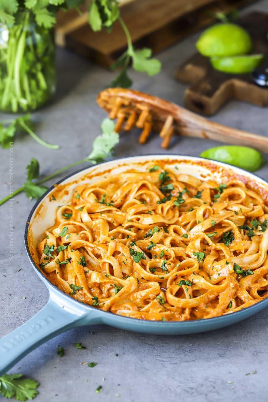 Creamy spicy chorizo pasta in skillet with cilantro garnish.