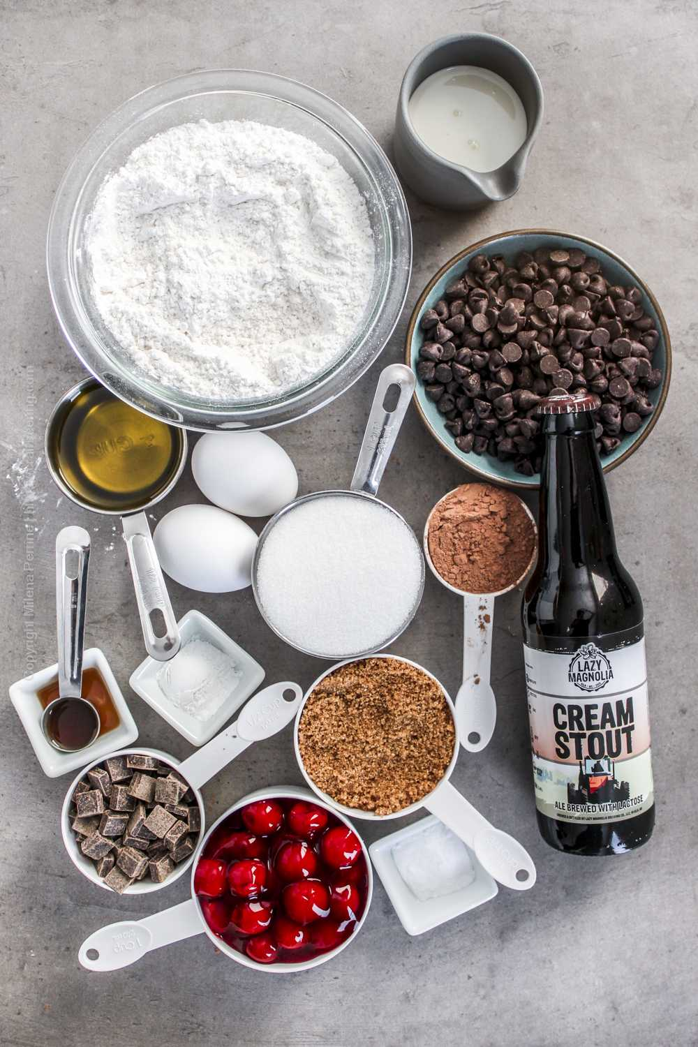 Raw ingredients for chocolate cherry cake - cherry pie filling, cake flour, olive oil, dark chocolate chips, cocoa powder, sugar, eggs. etc.