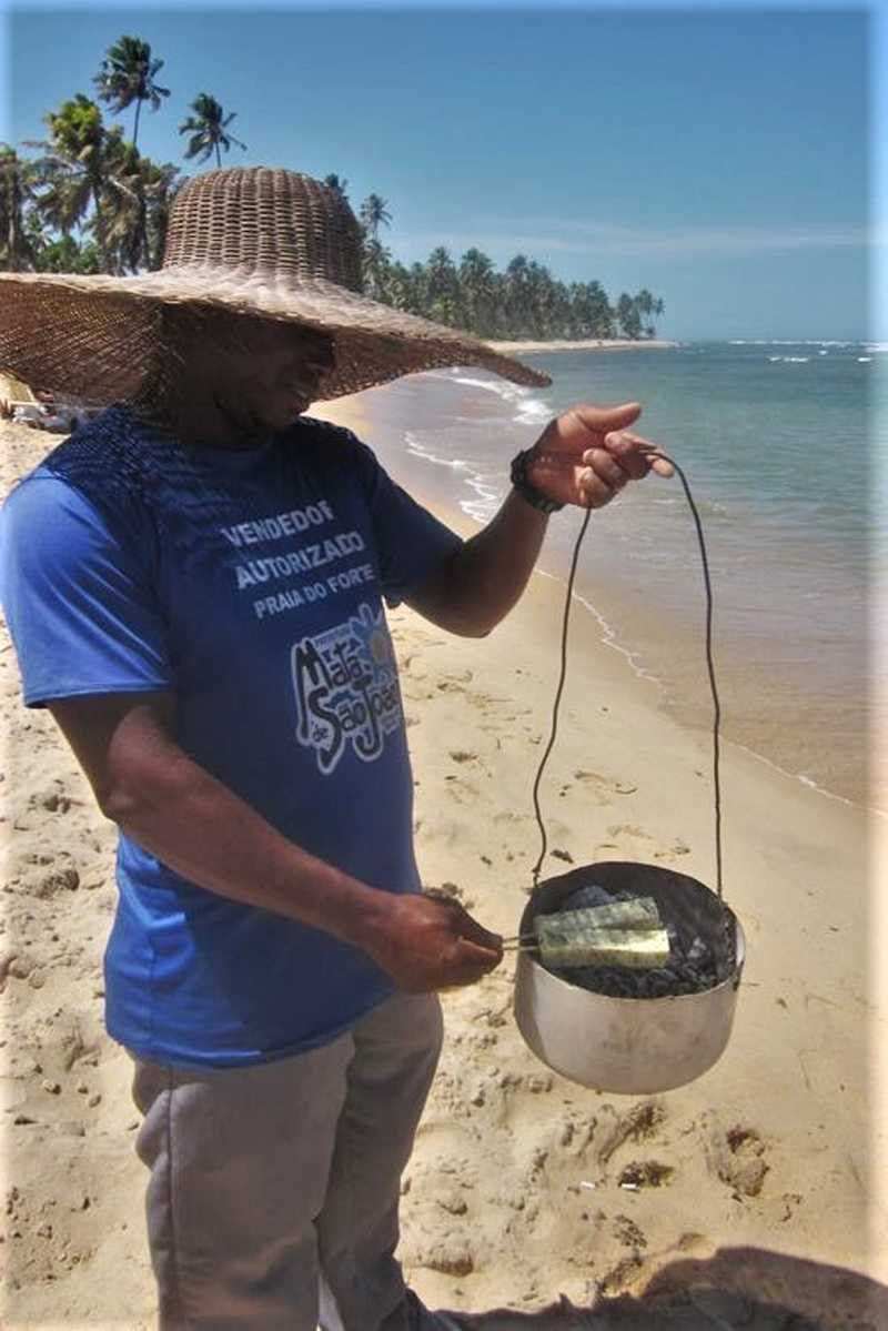 Man on beach in Brazil holding small portable charcoal grill for grilling queijo de coalho, with two skewers cooking.
