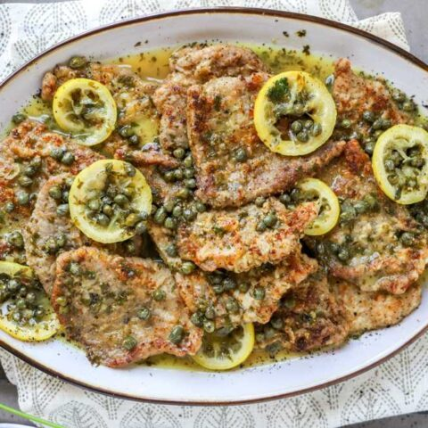 Veal piccata with the scallopini arranged on a platter.